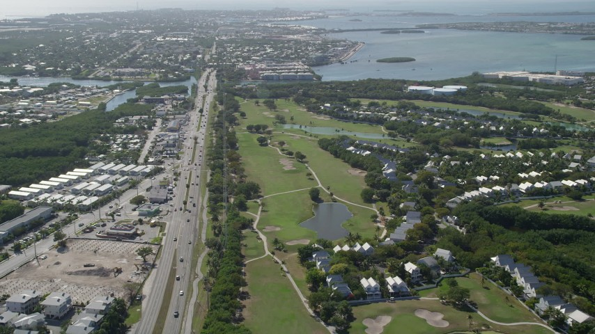 5K stock footage aerial video follow Overseas Highway to Stock Island and Key West Golf Club, Key West, Florida Aerial Stock Footage | AX0026_058