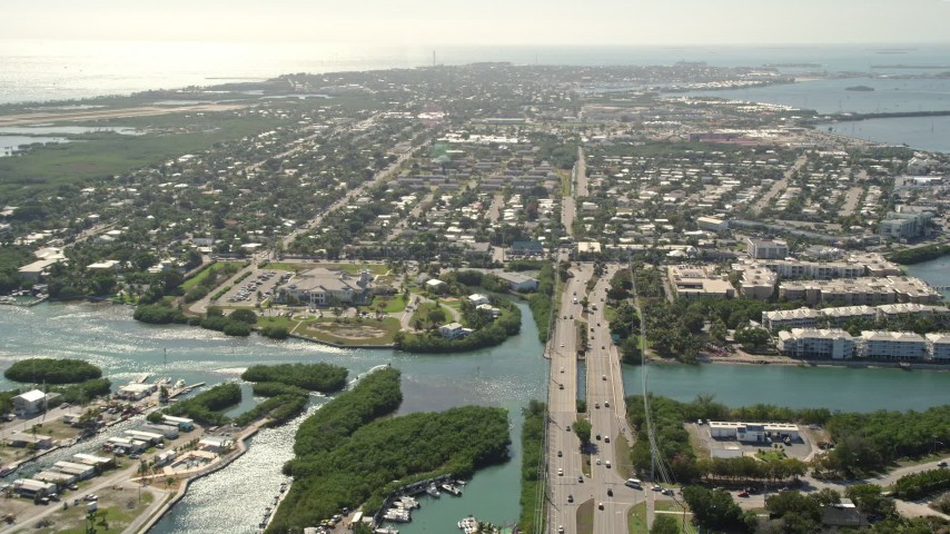 5K stock footage aerial video of following Overseas Highway, approaching the shore of Key West, Florida Aerial Stock Footage | AX0026_059