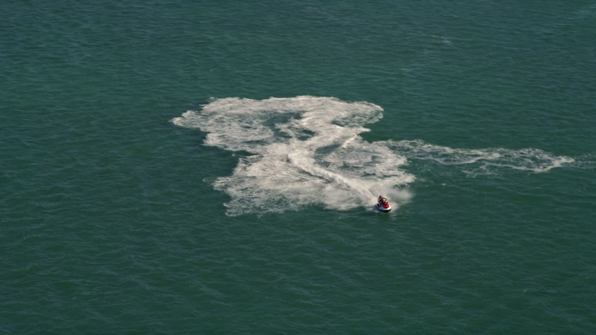 5K stock footage aerial video of a jet skier racing across the water in Key West, Florida Aerial Stock Footage | AX0026_088