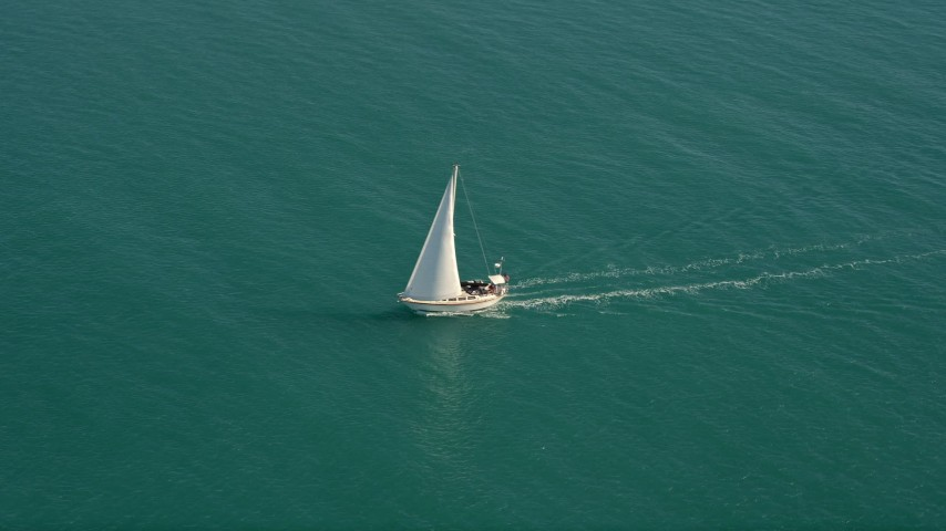 5K stock footage aerial video of following a sailboat near the shore of Key West, Florida Aerial Stock Footage | AX0026_096E