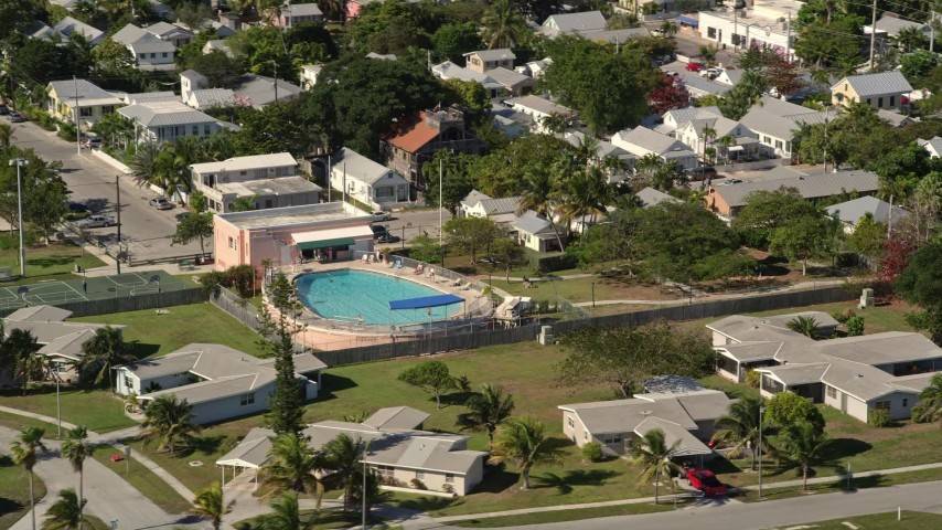 5K stock footage aerial video of flying by a large pool behind a house on Key West, Florida Aerial Stock Footage | AX0026_113