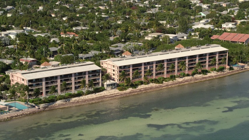 5K stock footage aerial video of flying by apartment buildings on the shore of Key West, Florida Aerial Stock Footage | AX0026_116