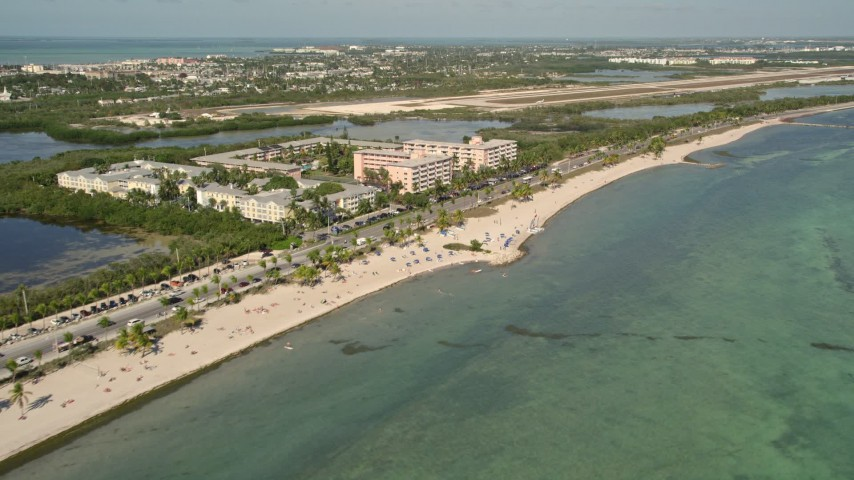 5K stock footage aerial video of sunbathers on Smathers Beach, Sheraton Suites Key West in Key West, Florida Aerial Stock Footage | AX0026_118