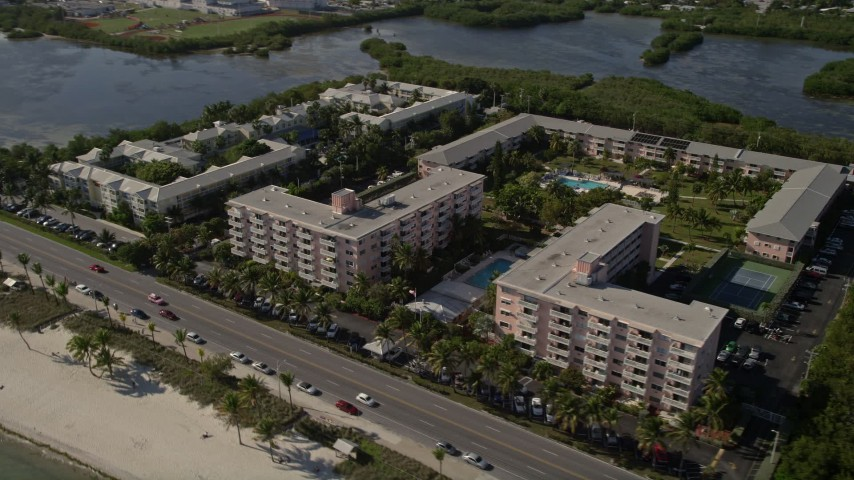5K stock footage aerial video of following coast toward apartment buildings, Sheraton Suites, Key West, Florida Aerial Stock Footage   AX0027_005
