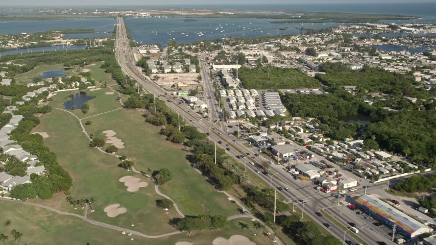 5K stock footage aerial video of following Overseas Highway through Stock Island, Key West, Florida Aerial Stock Footage | AX0027_031