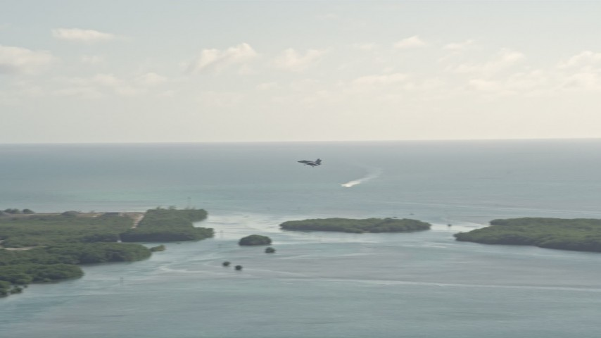 5K stock footage aerial video of tracking an F-18 landing at Naval Air Station Key West, Key West, Florida Aerial Stock Footage | AX0027_037
