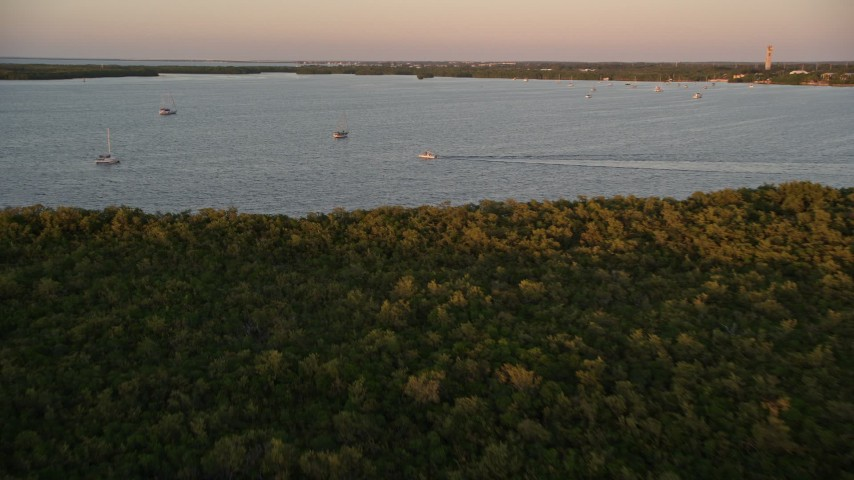5K stock footage aerial video of flying over mangroves, approaching sailboats and fishing boat at sunset, Key Largo, Florida Aerial Stock Footage | AX0028_033