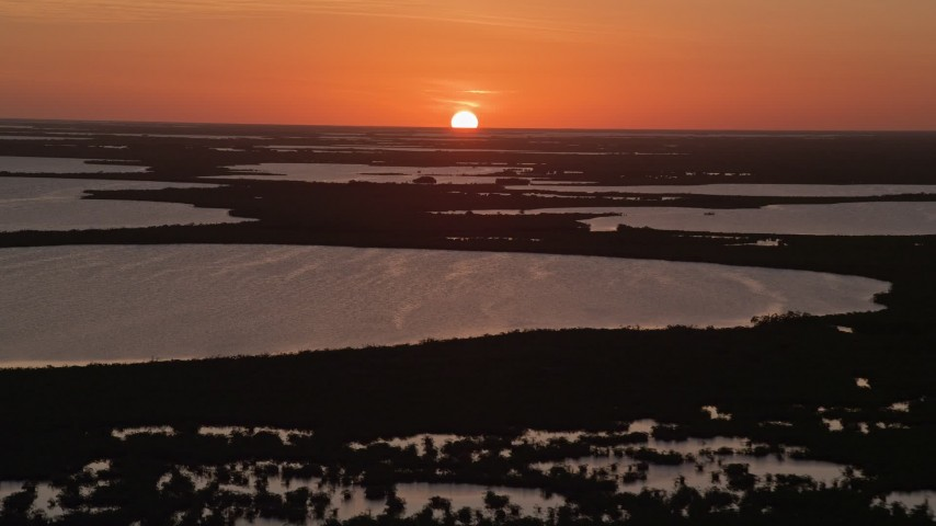 5K stock footage aerial video of descending toward the water and mangrove islands, Key Largo, Florida, sunset Aerial Stock Footage | AX0028_045E