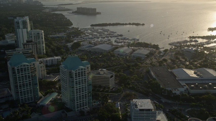 5K stock footage aerial video fly over office buildings, approach yacht clubs, Coconut Grove, Florida, sunrise Aerial Stock Footage | AX0029_006