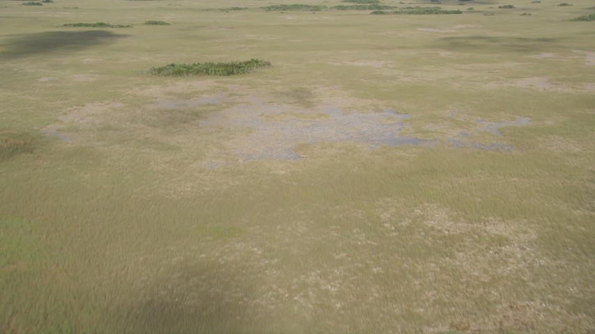 5K stock footage aerial video of flying over cloud shadows and water in marshland, Florida Everglades, Florida Aerial Stock Footage | AX0030_034
