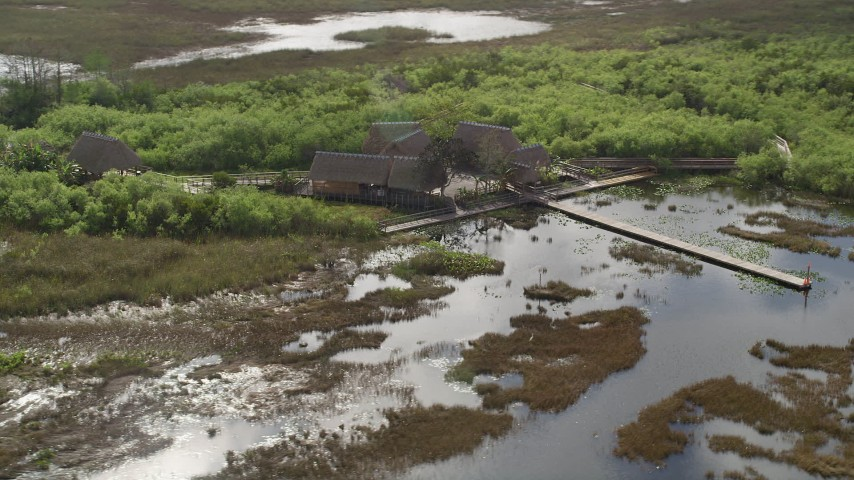 5K stock footage aerial video of flying away from huts, dock on the marshland, Florida Everglades, Florida Aerial Stock Footage | AX0030_062