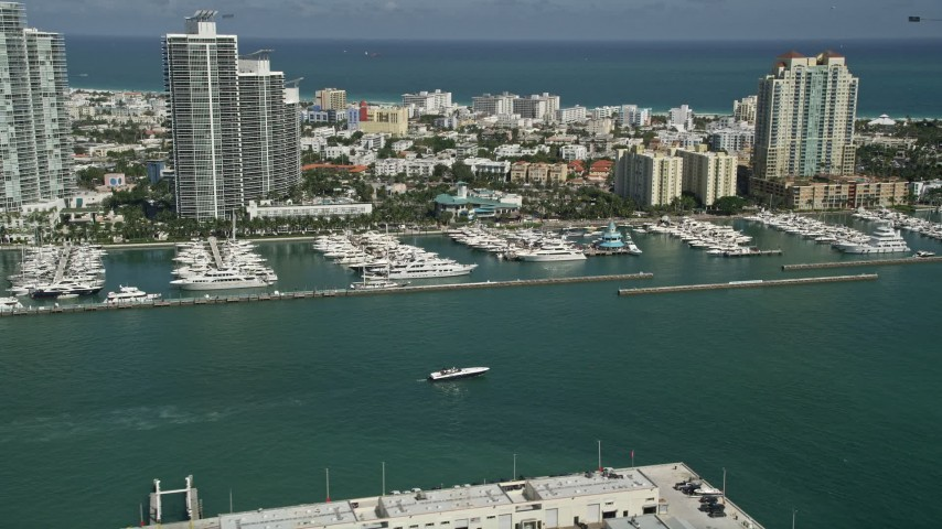 Flying by yachts docked at Miami Beach Marina, South Beach, Miami Beach, Florida Aerial Stock Footage | AX0031_047