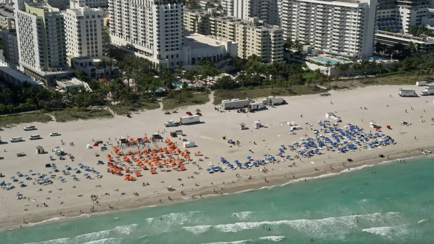 5K stock footage aerial video of flying by sunbathers, South Beach, Miami Beach, Florida Aerial Stock Footage | AX0031_054