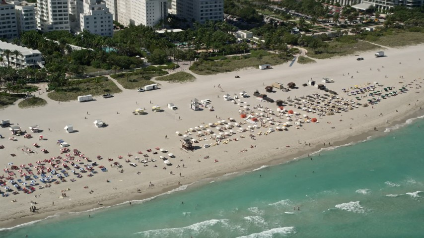 5K aerial video of flying by sunbathers, South Beach, Miami Beach, Florida Aerial Stock Footage | AX0031_055