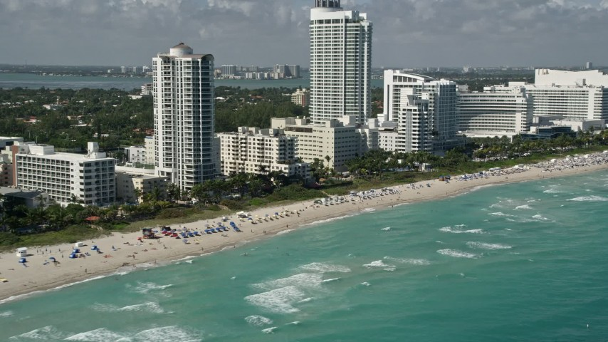 5K stock footage aerial video of flying by the beach near Fontainebleau Miami Beach, Miami Beach, Florida Aerial Stock Footage AX0031_058