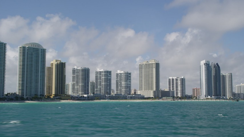 5K stock footage aerial video of flying by condominium complexes on the shore, Sunny Isles Beach, Florida Aerial Stock Footage | AX0031_076