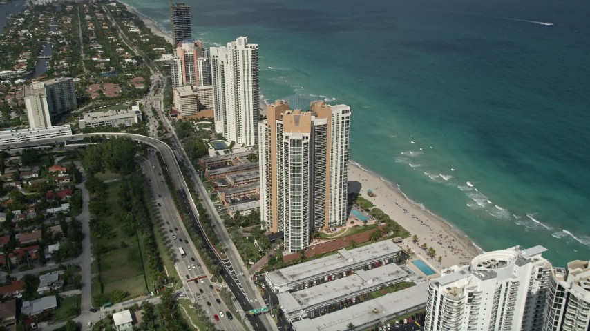 5K stock footage aerial video of approaching condominium complex on shore, tilt down, Sunny Isles Beach, Florida Aerial Stock Footage | AX0031_085