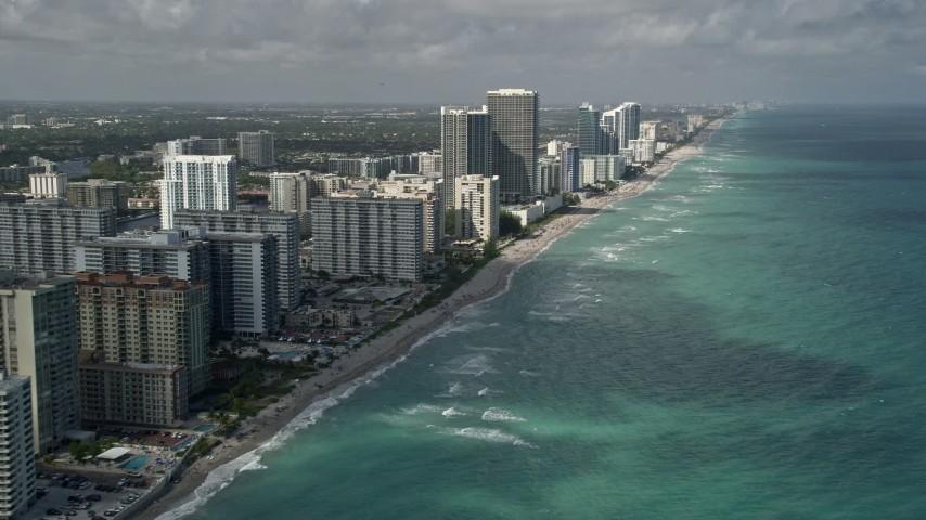 5K stock footage aerial video of following beach, approaching condominium complex, Hallandale Beach, Florida Aerial Stock Footage | AX0031_089