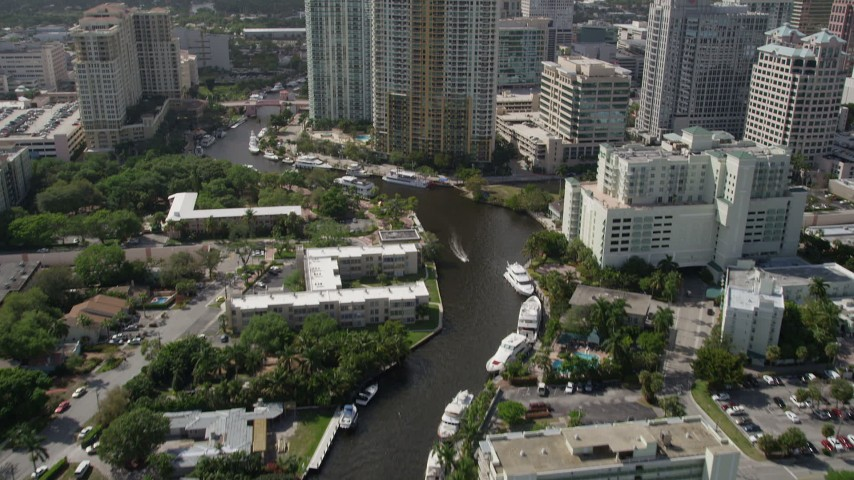 5K stock footage aerial video of following New River past mansions, revealing Downtown Fort Lauderdale, Florida Aerial Stock Footage | AX0031_114