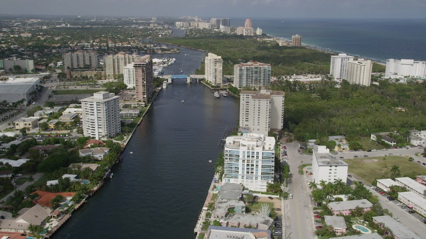 5K aerial video follow canal past apartments, East Sunrise Boulevard bridge, Fort Lauderdale, Florida Aerial Stock Footage | AX0031_136