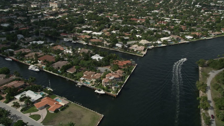 5K stock footage aerial video of following canal, tilt down on mansions, Fort Lauderdale, Florida Aerial Stock Footage | AX0031_140
