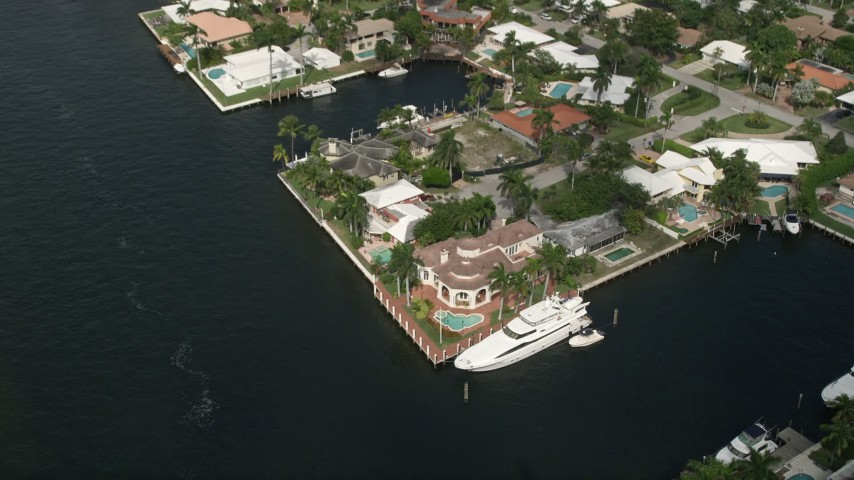 5K aerial video of approaching mansion by canal and a yacht, tilt down, Fort Lauderdale, Florida Aerial Stock Footage | AX0031_141