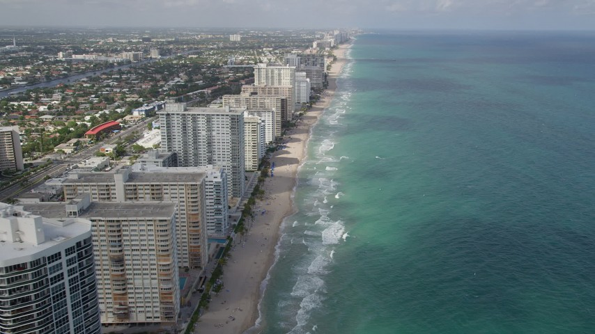 5K aerial video of flying by apartment buildings, revealing beach, coastline, Fort Lauderdale, Florida Aerial Stock Footage AX0031_143