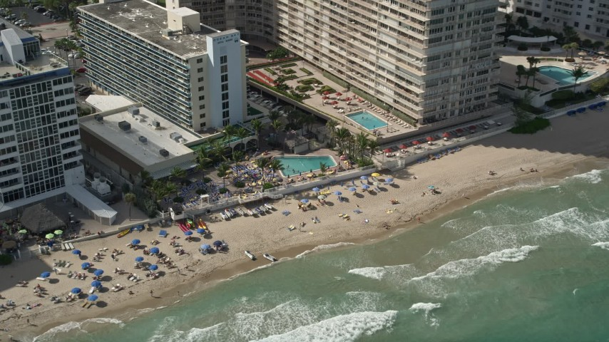 5K aerial video of sunbathers by Ocean Sky Hotel and Resort, Fort Lauderdale, Florida Aerial Stock Footage | AX0031_145