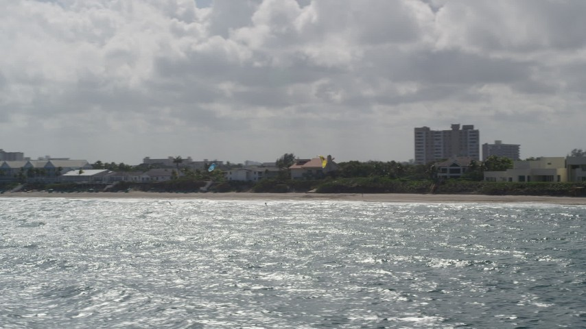 5K stock footage aerial video fly by kite surfers near coast, reveal Hillsboro Inlet Light, Hillsboro Beach, Florida Aerial Stock Footage | AX0031_170