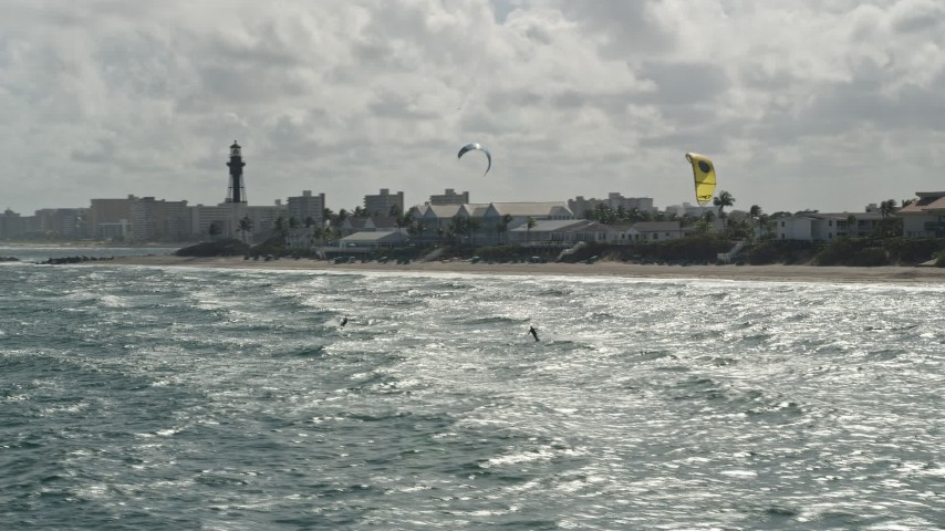 5K stock footage aerial video fly by kite surfers near coast, reveal Hillsboro Inlet Light, Hillsboro Beach, Florida Aerial Stock Footage | AX0031_170E