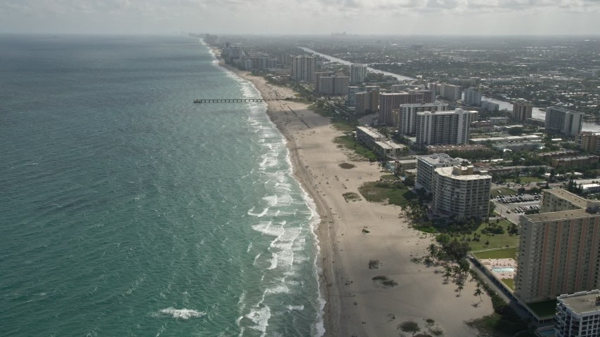 5K stock footage aerial video of following beach, approaching Pompano Beach Pier, Pompano Beach, Florida Aerial Stock Footage | AX0031_179