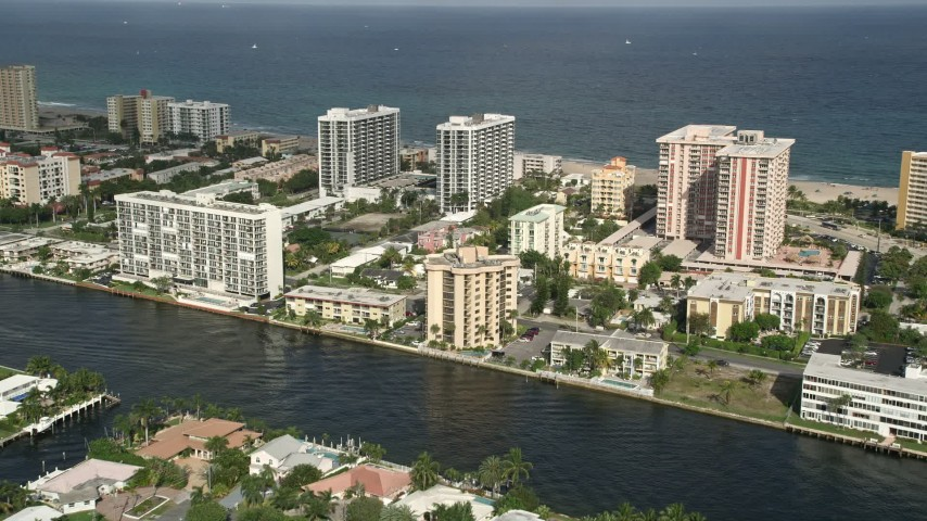 5K stock footage aerial video of flying by condominium complexes, approaching the coast, Pompano Beach, Florida Aerial Stock Footage | AX0032_004