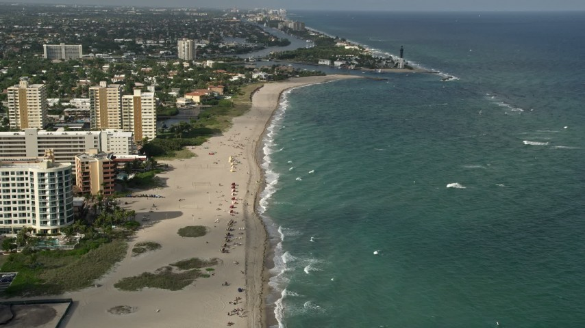 5K stock footage aerial video approach Hillsboro Inlet Light, tilt down to sunbathers, Pompano Beach, Florida Aerial Stock Footage | AX0032_006