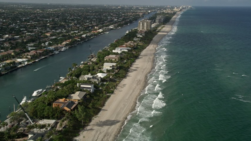 5K stock footage aerial video of flying by homes near the beach, revealing coastline, Hillsboro Beach, Florida Aerial Stock Footage | AX0032_009