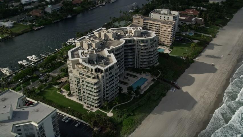 5K stock footage aerial video of following the beach, tilt down to condominium complex, Hillsboro Beach, Florida Aerial Stock Footage | AX0032_011