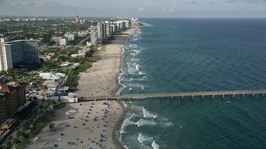 5K stock footage aerial video follow the beach, over Deerfield Beach Fishing Pier, Deerfield Beach, Florida Aerial Stock Footage   AX0032_017