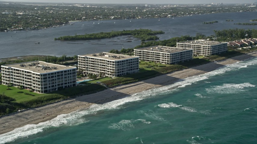 5K stock footage aerial video of flying by coastal condominium complexes, Palm Beach, Florida Aerial Stock Footage   AX0032_068