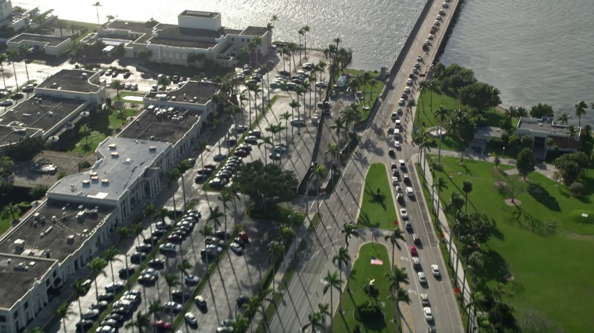 5K stock footage aerial video fly over Royal Poinciana Way, reveal Flagler Memorial Bridge, Palm Beach, Florida Aerial Stock Footage | AX0032_084