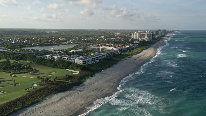 5K stock footage aerial video of flying along the coast by apartment buildings, Juno Beach, Florida Aerial Stock Footage | AX0032_127