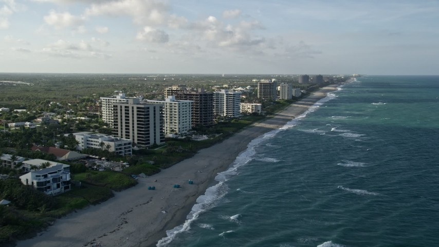5K stock footage aerial video of following the beach, approaching condominium complexes, Juno Beach, Florida Aerial Stock Footage | AX0032_128