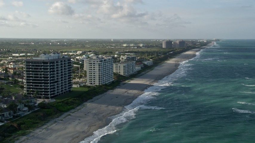 5K stock footage aerial video of following the beach by apartment buildings, Juno Beach, Florida Aerial Stock Footage | AX0032_129