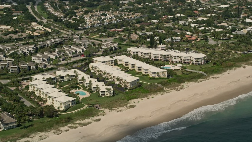 5K stock footage aerial video of flying by beachside condominium complexes, Vero Beach, Florida Aerial Stock Footage | AX0033_054