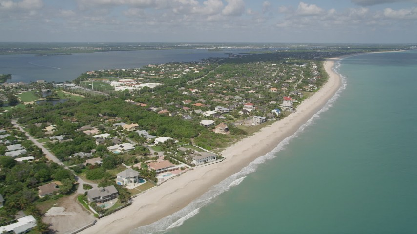 5K stock footage aerial video of following the beach by residential neighborhoods, Vero Beach, Florida Aerial Stock Footage   AX0033_056