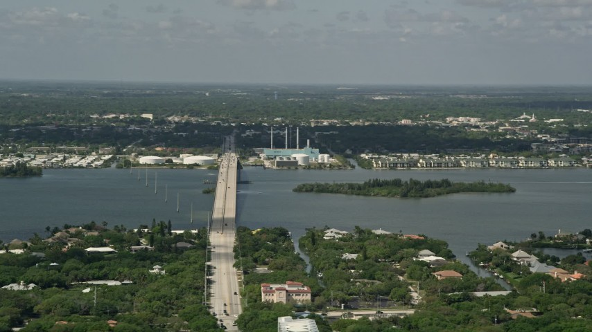 5K stock footage aerial video of flying by a bridge and power plant, Vero Beach, Florida Aerial Stock Footage   AX0033_060