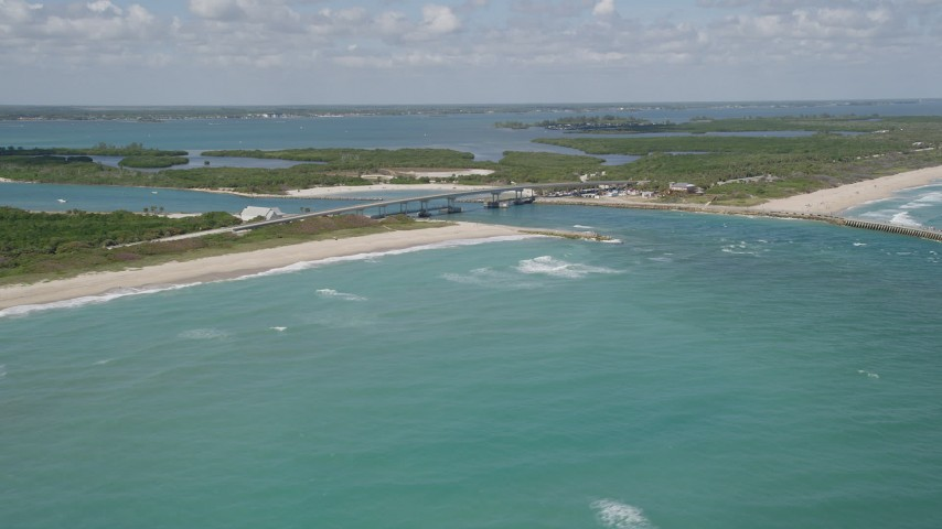 5K stock footage aerial video of flying by a bridge spanning an inlet with crystal blue waters, Vero Beach, Florida Aerial Stock Footage   AX0033_065