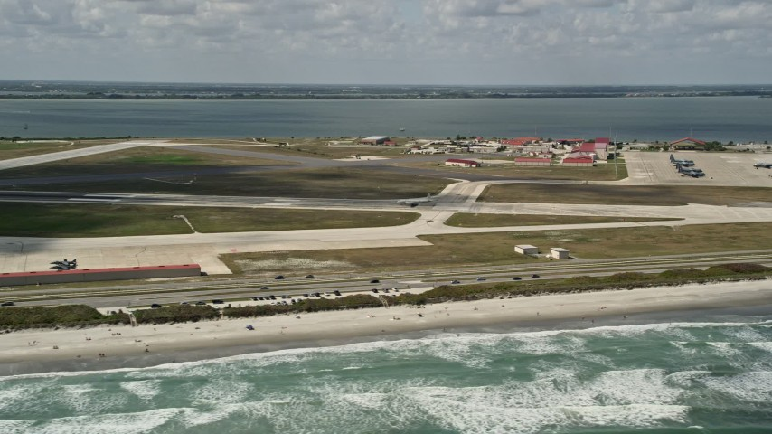 5K stock footage aerial video fly by a turboprop plane on the runway, Patrick Air Force Base, Florida Aerial Stock Footage AX0034_004 | Axiom Images