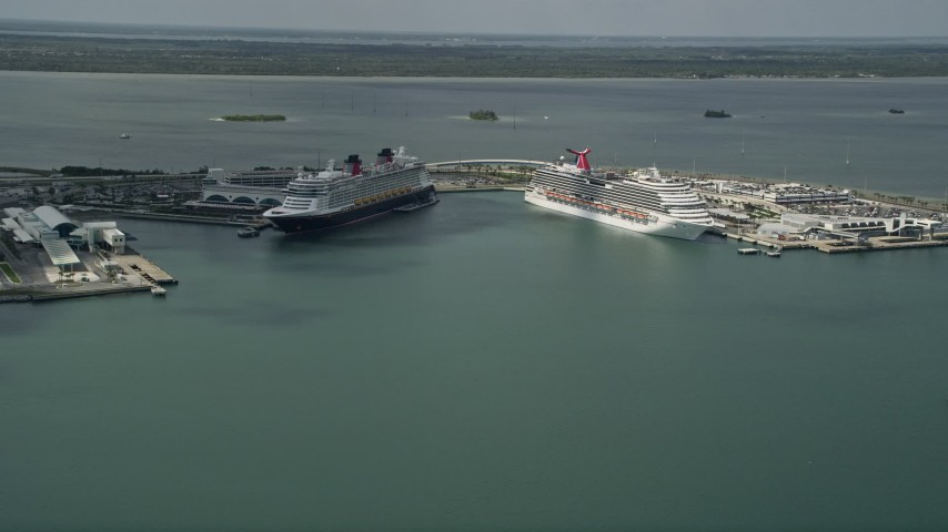 5K stock footage aerial video of approaching Carnival and Disney Cruise Ships, Port Canaveral, Florida Aerial Stock Footage | AX0034_017