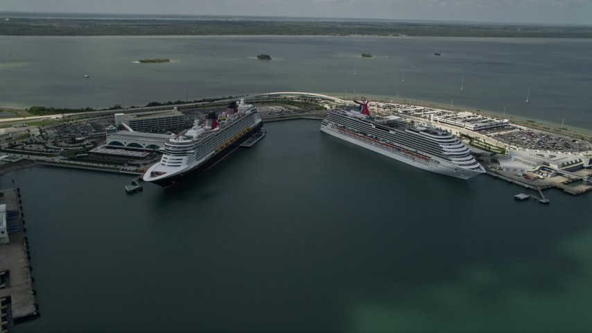 5K stock footage aerial video of approaching a Disney and Carnival Cruise Ship, Port Canaveral, Florida Aerial Stock Footage | AX0034_018