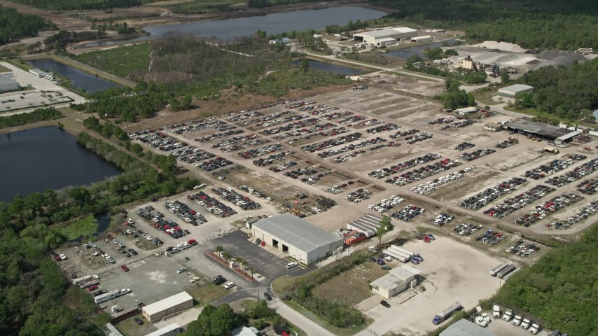 5K stock footage aerial video of approaching an auto salvage lot, Cocoa, Florida Aerial Stock Footage | AX0034_030