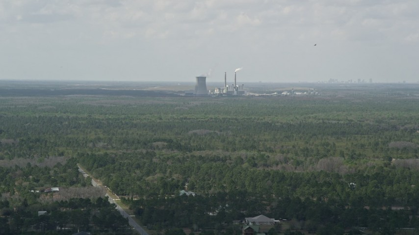 5K stock footage aerial video fly over trees toward a coal fired power generation facility, Orlando, Florida Aerial Stock Footage | AX0034_072
